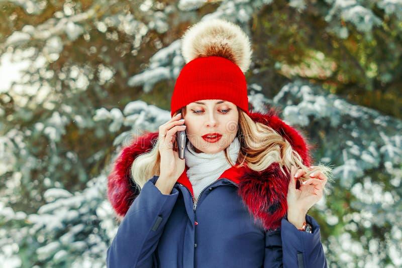 Vinterflicka som talar på telefonen arkivfoton