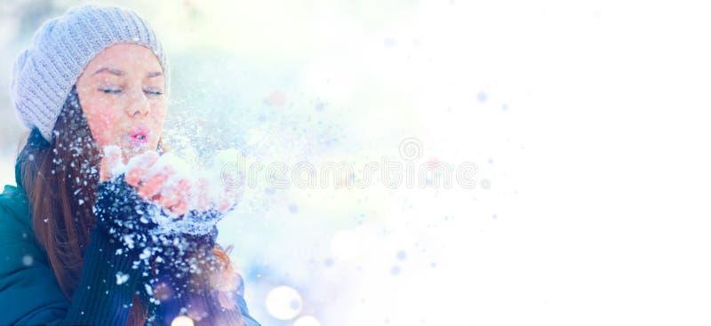 Vinterflickastående Parkerar den glade modellflickan för skönhet som blåser snö och att ha gyckel i vinter härligt tyckande om na royaltyfri fotografi
