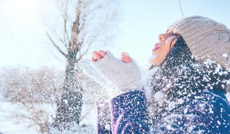 Vinterflickastående Parkerar den glade modellflickan för skönhet som blåser snö och att ha gyckel i vinter härligt tyckande om na arkivfoto