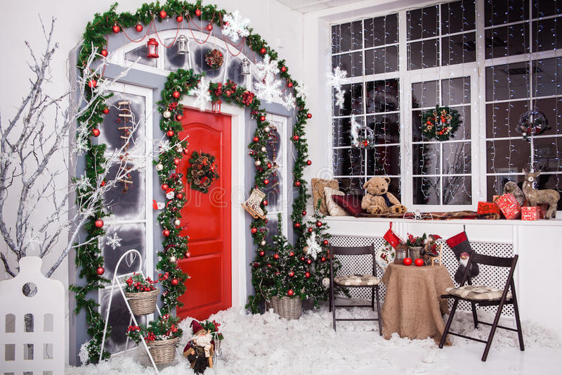 Vintergarnering Röd dörr med julkransen royaltyfria foton