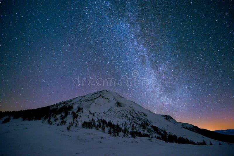 Vintergatan över de snöig maxima av bergen royaltyfria bilder