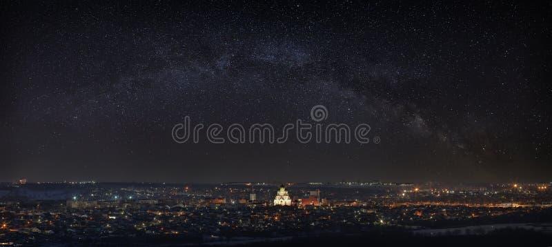 Vintergatan över staden Ljusa stjärnor i natthimlen Gatorna tänds av lyktor Panoramautsikt av den ortodoxa kyrkan arkivfoto