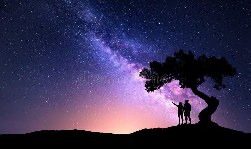Vintergatan med folk under trädet på hilen fotografering för bildbyråer