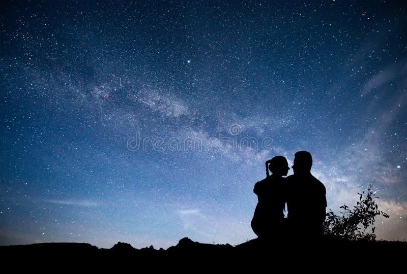 Vintergatan med konturn av folk Landskap med stjärnklar himmel för natt Stående man och kvinna på berget med stjärnan arkivfoton