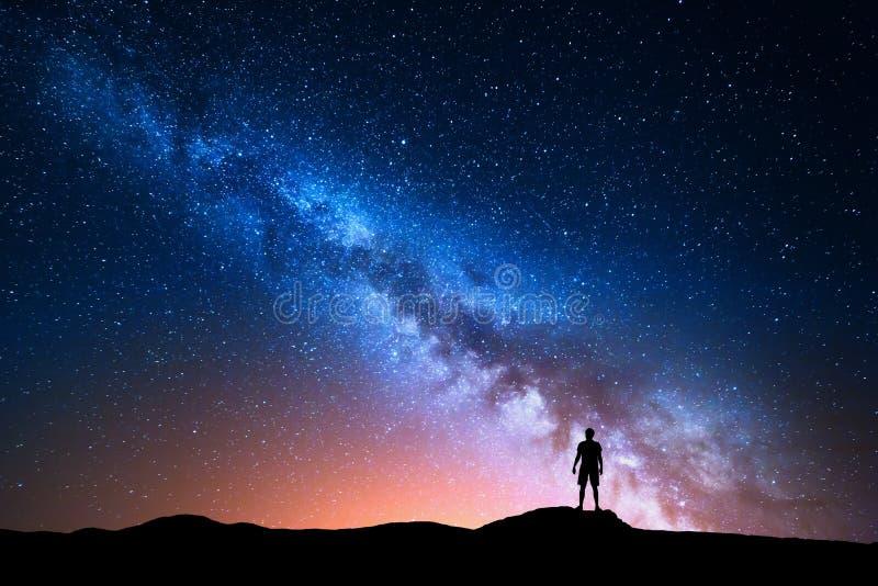 Vintergatan och kontur av den ensamma mannen för bildinstallation för bakgrund härligt bruk för tabell för foto för natt för ligg royaltyfri fotografi