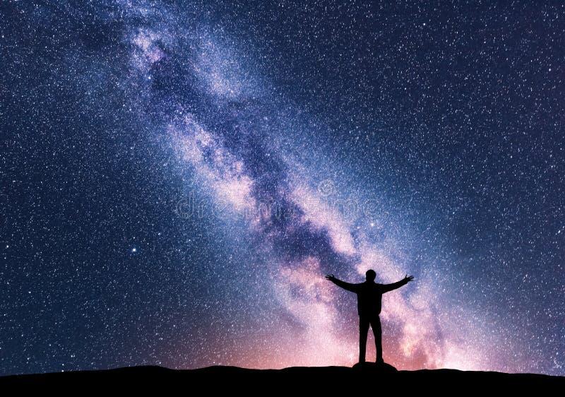 Vintergatan och kontur av en stående lycklig man arkivfoton