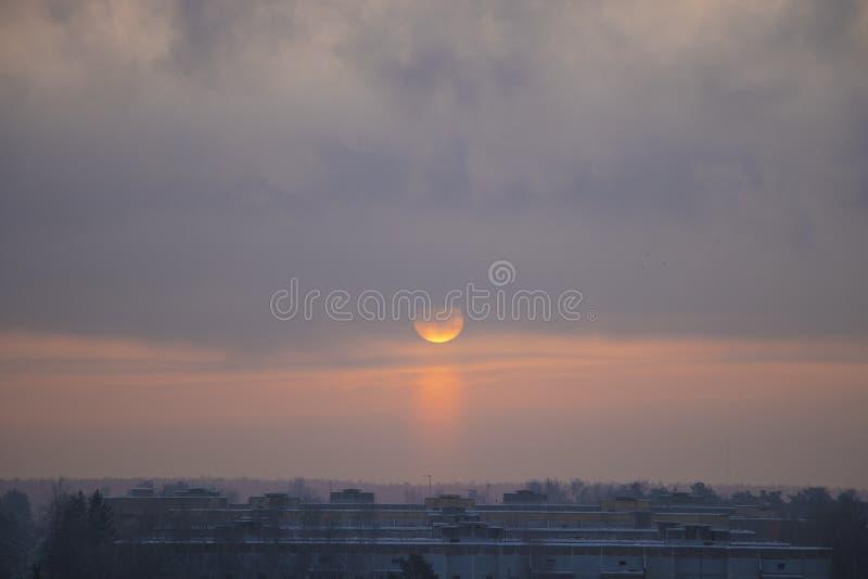 Vintergryning och den frostiga dimman Sollöneförhöjningarna över en liten stad royaltyfri foto