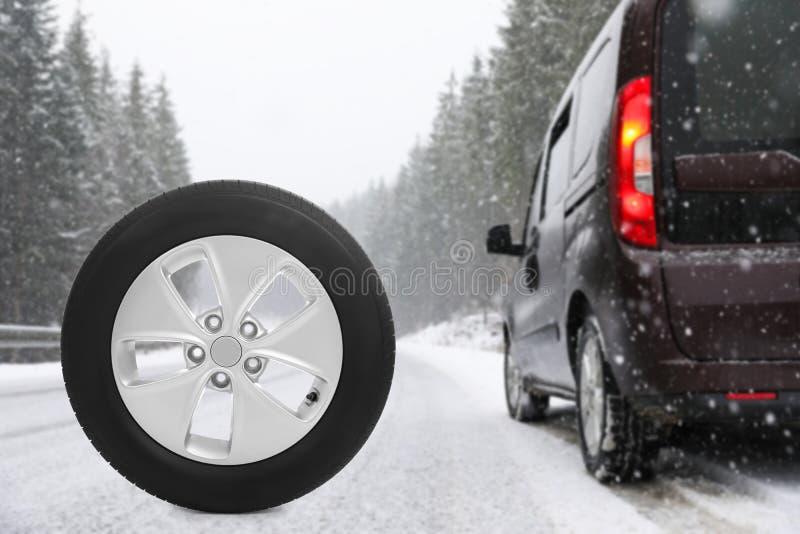 Vintergummihjul nära den brutna bilen på skoghuvudvägen under snöfall royaltyfri foto