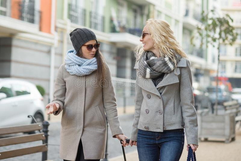 Vinterhöststående av två le unga kvinnor som promenerar en stadsgata fotografering för bildbyråer