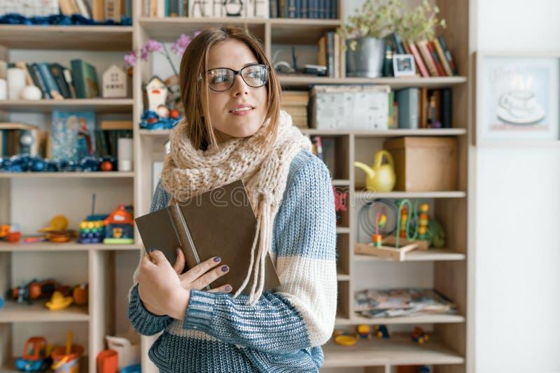 Vinterhöststående av unga härliga bärande exponeringsglas för flickastudent i stucken varm halsduk- och tröjaläsebok inomhus arkivfoto