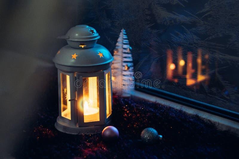 Vinterjulafton Frostat fönster med julgarneringen Lykta med en tänd stearinljus nära fönstret med frostiga modeller på arkivbild