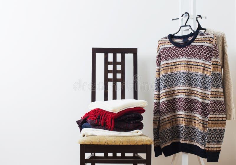 Vinterkläder på stol mot vit väggbakgrund royaltyfria foton