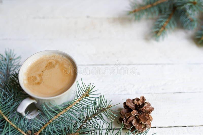 Vinterkort med kaffekoppen och att sörja trädet på vit träbakgrund, kopieringsutrymme royaltyfri foto