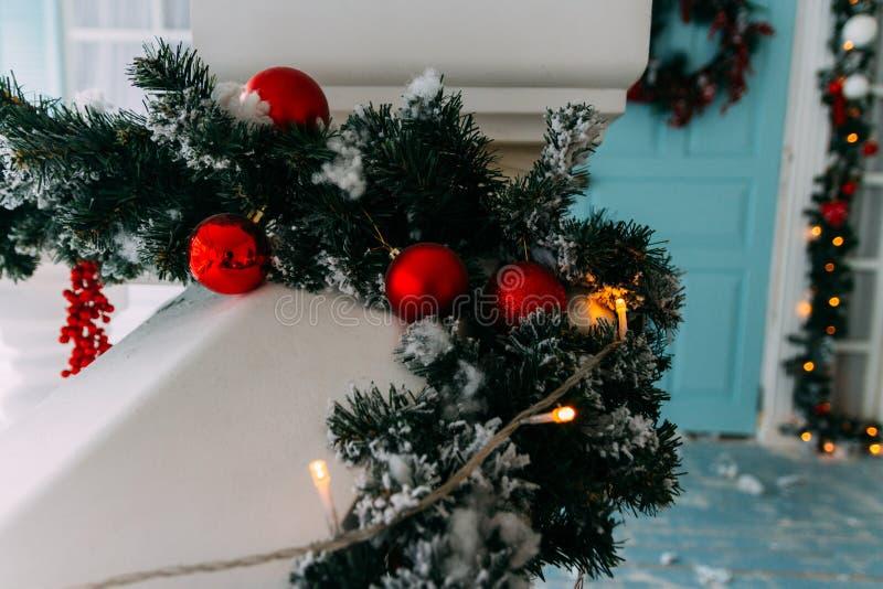 Vinterkransen som hänger på en dörr av huset som dekoreras av jul, sörjer filialen med röda struntsaker och dekorativ snö royaltyfri fotografi