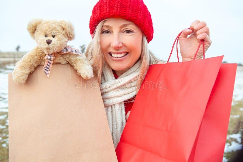 Vinterkvinna som rymmer återförsäljnings- shopping- eller gåvapåsar arkivbilder
