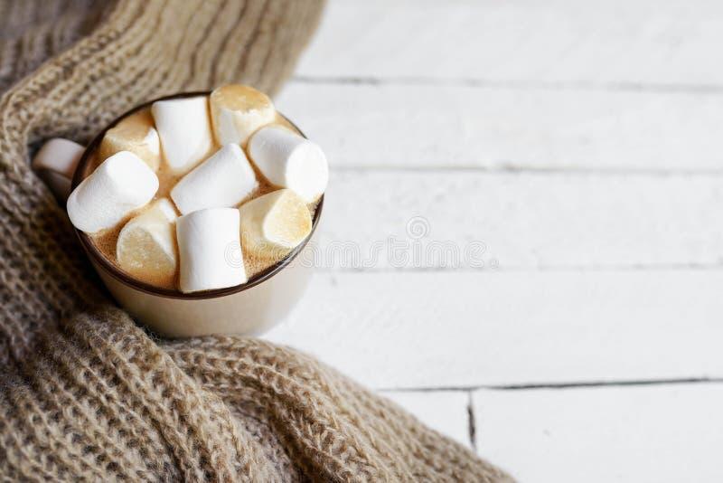 Vinterlägenheten lägger med den rutiga varma halsduken, varm kopp av kakao på vit träbakgrund med utrymme för kopia arkivfoton