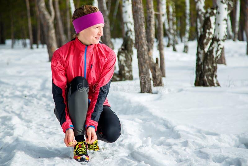 Vinterlöpare som får den klara running bindande skon, snör åt Härlig konditionmodellutbildning utanför Kopiera avstånd på snow arkivbild