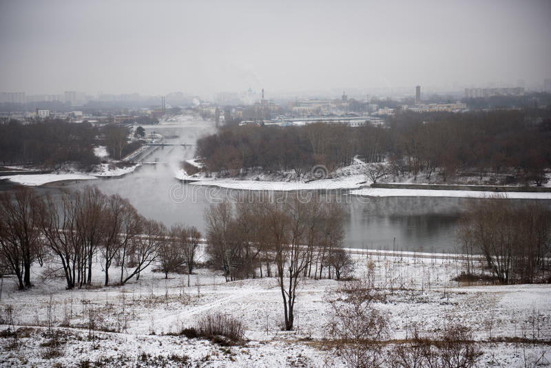 Vinterlandskap av dentäckte fält, träd och floden i den tidiga dimmiga morgonen fotografering för bildbyråer