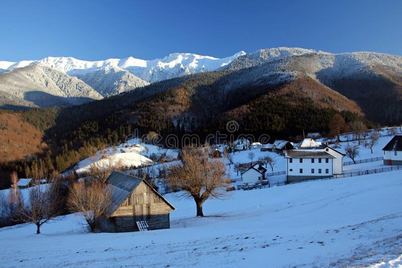 Vinterlandskap i bergen - med den lilla traditionella byn arkivfoto