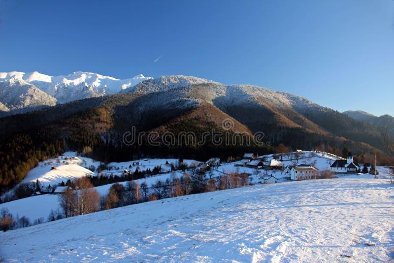 Vinterlandskap i bergen - med den lilla traditionella byn arkivbild