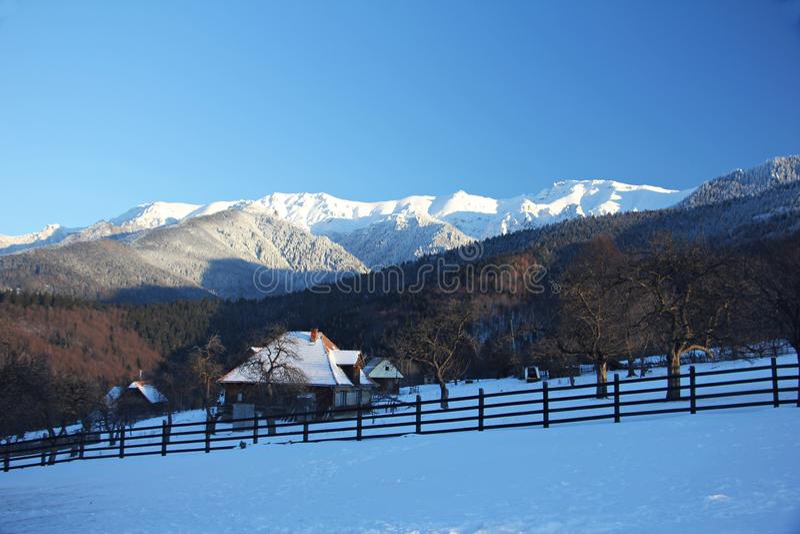 Vinterlandskap i bergen - med den lilla traditionella byn royaltyfri foto