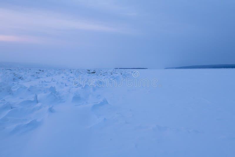 Vinterlandskap i blåa signaler med ridged is på den djupfrysta floden royaltyfri fotografi