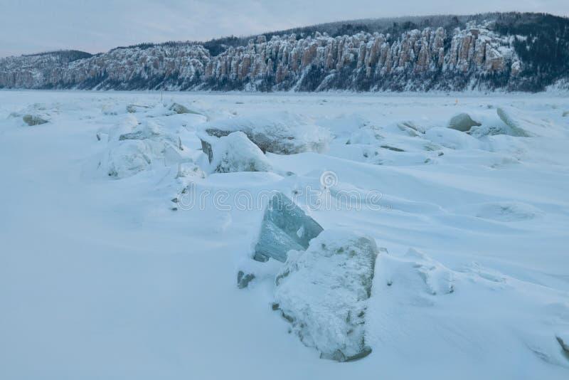 Vinterlandskap i blåa signaler med ridged is på den djupfrysta floden på skymning arkivfoto
