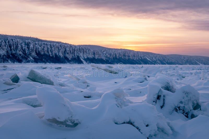 Vinterlandskap i purpurfärgade signaler med ridged is på den djupfrysta floden royaltyfria bilder