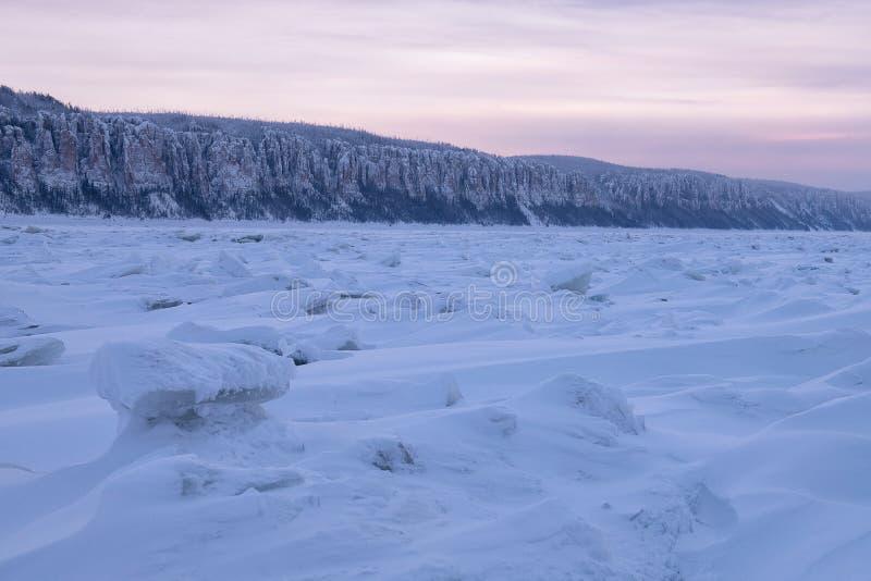 Vinterlandskap i purpurfärgade signaler med ridged is på den djupfrysta floden på solnedgången royaltyfria bilder