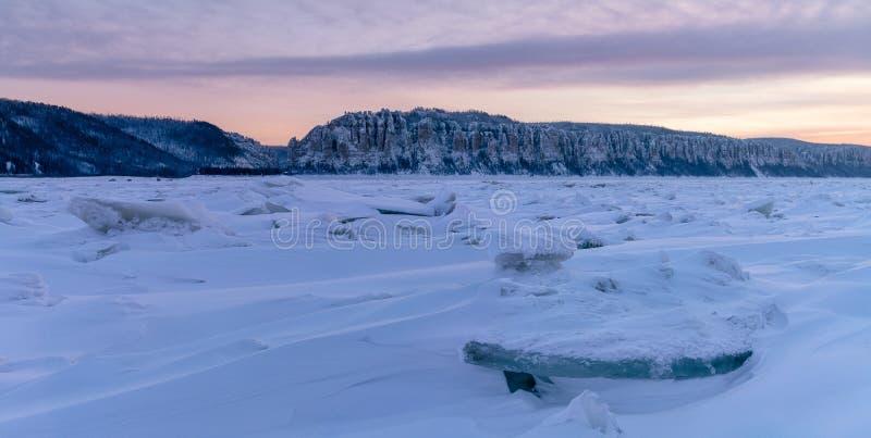 Vinterlandskap i rosa signaler med ridged is på den djupfrysta floden på solnedgången arkivfoton