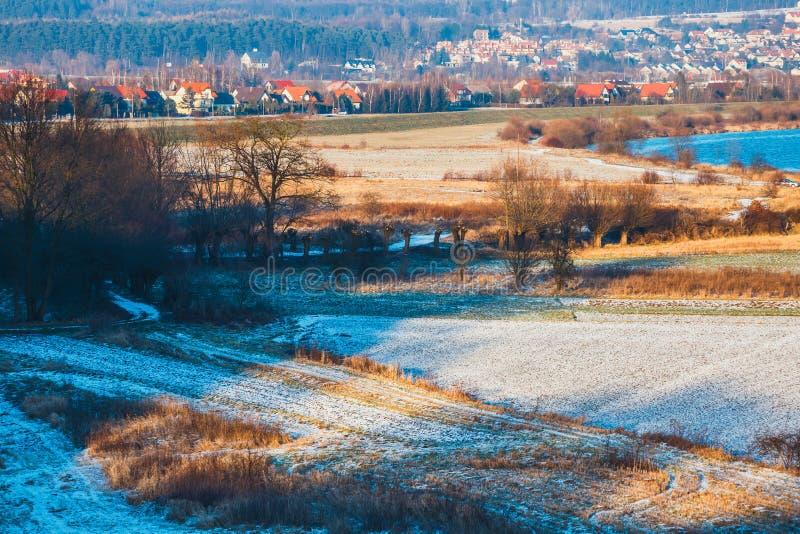 Vinterlandskap med det rimfrost täckte fältet arkivfoto