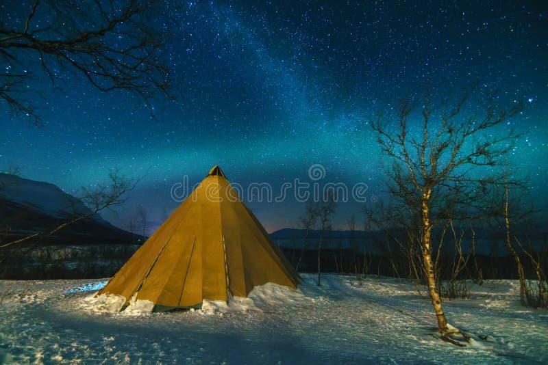 Vinterlandskap med eskimåtältet och nordliga ljus arkivfoto