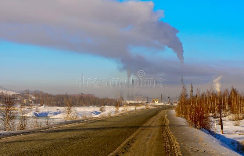 Vinterlandskap med industriell rök royaltyfri bild