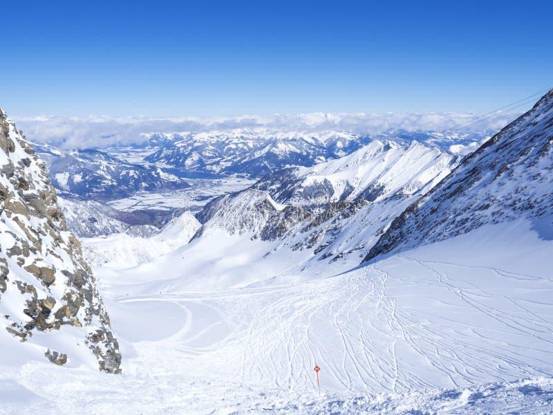 Vinterlandskapet med snålskjutspisten och sikten på dolda lutningar för snö och blå himmel, med flyg- sikt av Zell är ser sjön arkivfoto