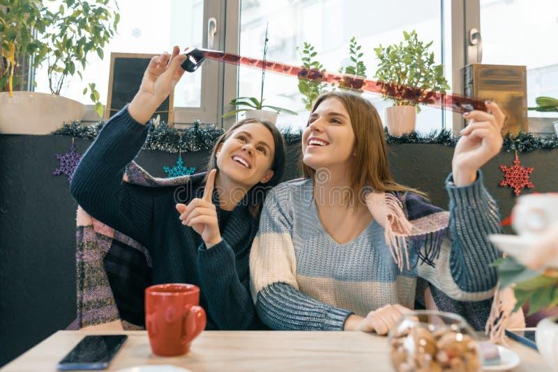 Vinterlivsstilflickor i kafét som har gyckel som ser gamla filmrullar arkivfoto