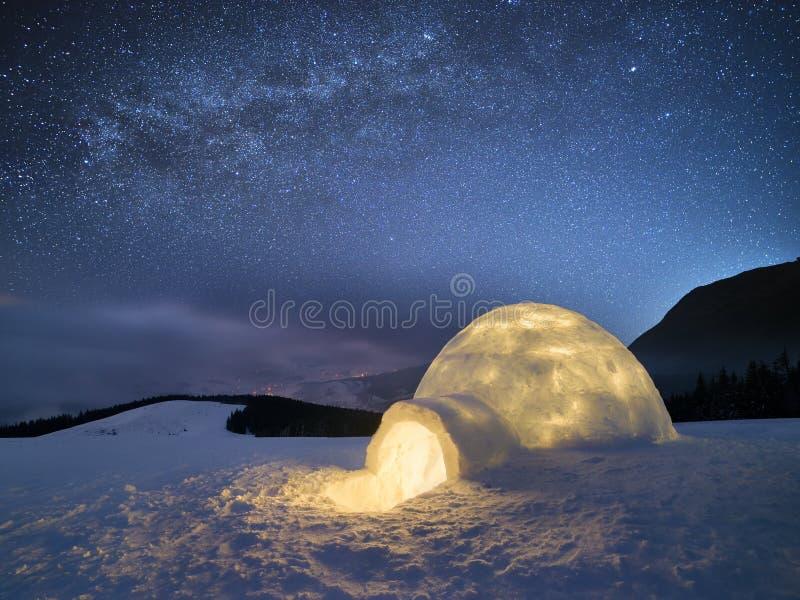 Vinternattlandskap med en snöigloo och en stjärnklar himmel royaltyfri bild