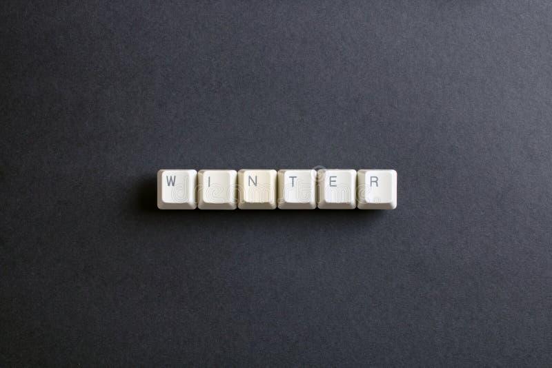 Vinterordet är skriftligt med knappen för datortangenter Lekmanna- sikt för lägenhet fotografering för bildbyråer