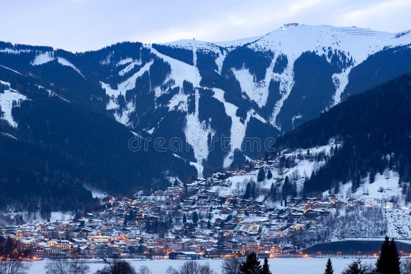 Vinterpanorama av Zell f.m. ser att staden med skidar lutningar och berg som täckas i snö Berömt skidar semesterorten i Österrike royaltyfri foto