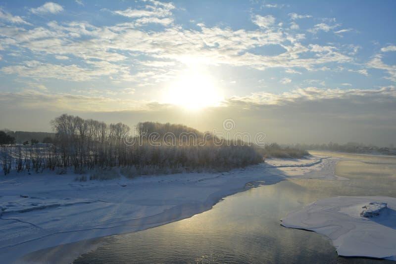 Vinterplats med början av solnedgången Floden är delvist under is royaltyfria foton