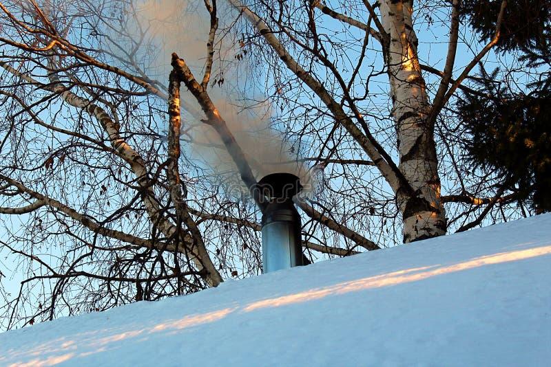 Vinterrök kommer ut ur lampglaset hem- ugnugn arkivbild