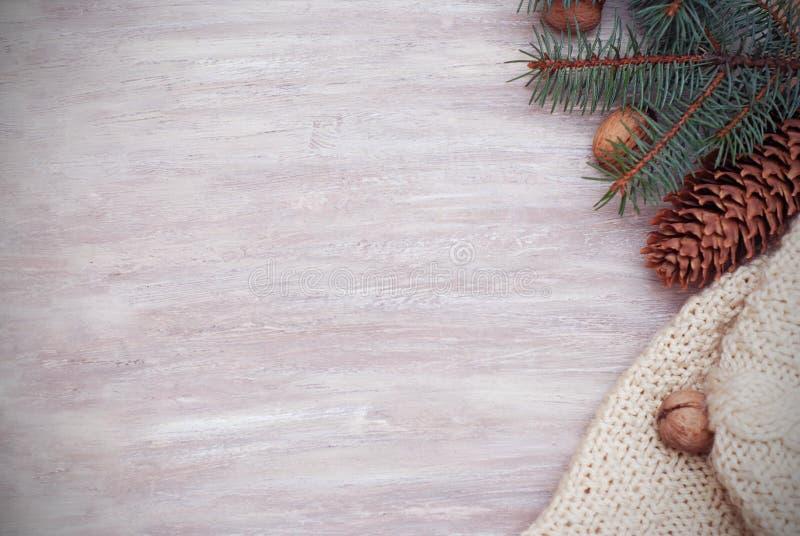 VintersäsongCristmas ram med granfilialer, Pinecones och den stack tröjan på träbakgrunden arkivbilder