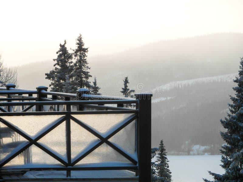 Vintersikten av balkongen av huset och skidar lutningen royaltyfria foton