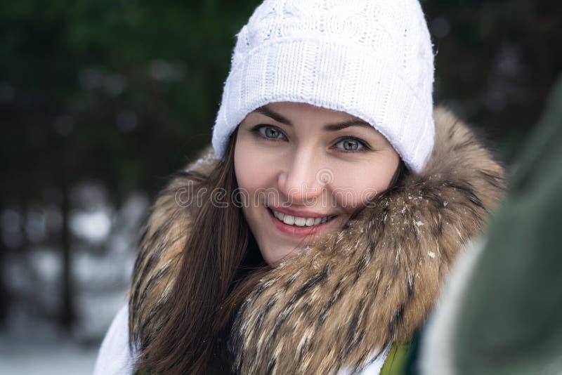 Vintersjälvporträtt av en ung kvinna på en bakgrund av barrskogen på en solig dag Selfie flicka i omslag med päls som stickas arkivbilder