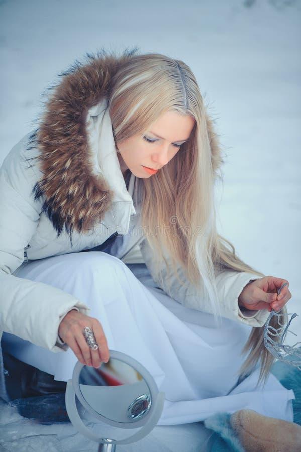 Vinterskönhetkvinna Härlig flicka för modemodell med snöfrisyren och makeup i den festliga makeupen och manikyren för vinterskog royaltyfria bilder