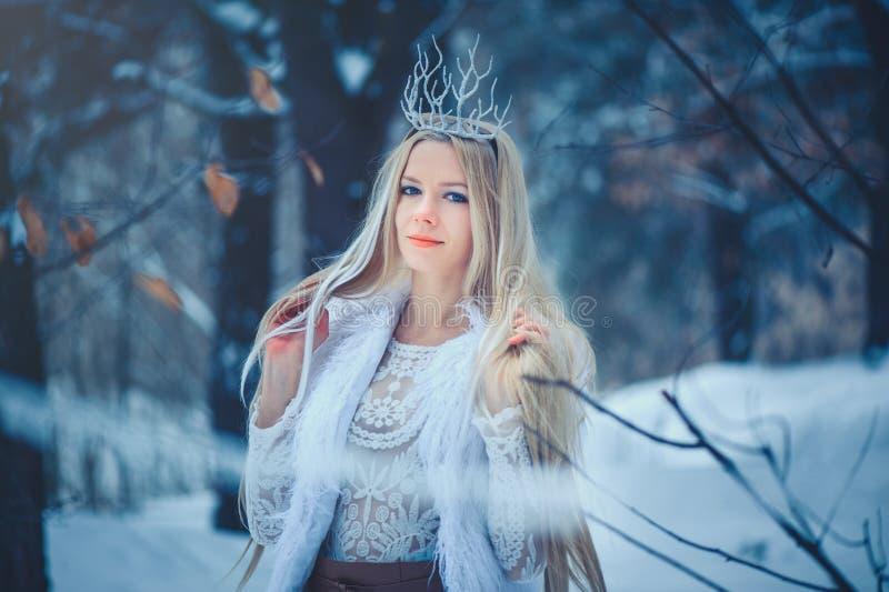 Vinterskönhetkvinna Härlig flicka för modemodell med snöfrisyren och makeup i den festliga makeupen och manikyren för vinterskog royaltyfri foto