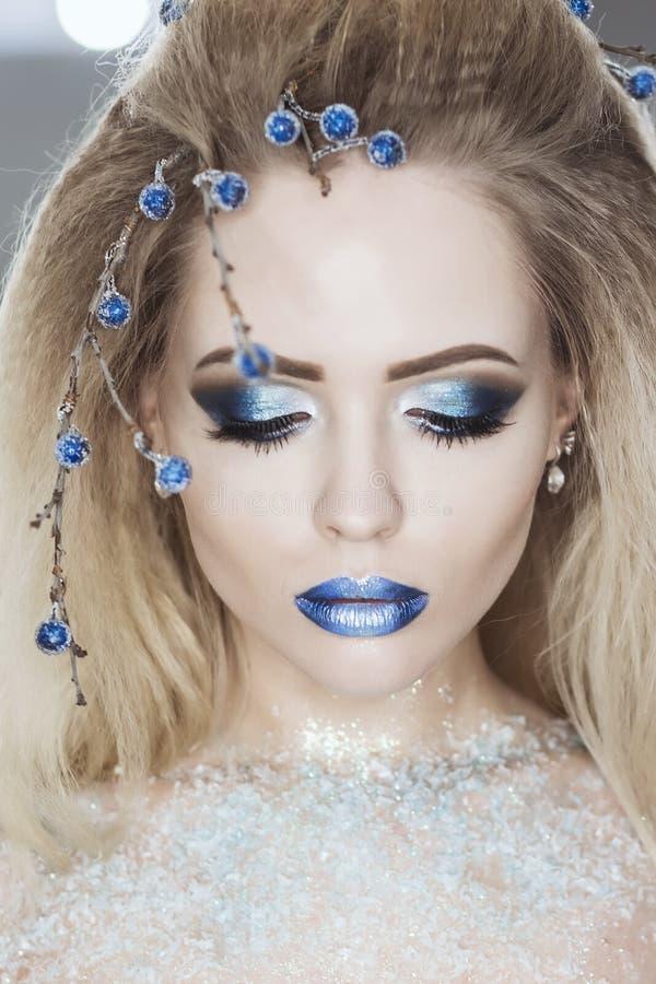 Vinterskönhetkvinna Julflickamakeup Feriesmink Stående för högt mode för snödrottning över blåttsnöbakgrund ögonskugga arkivfoton