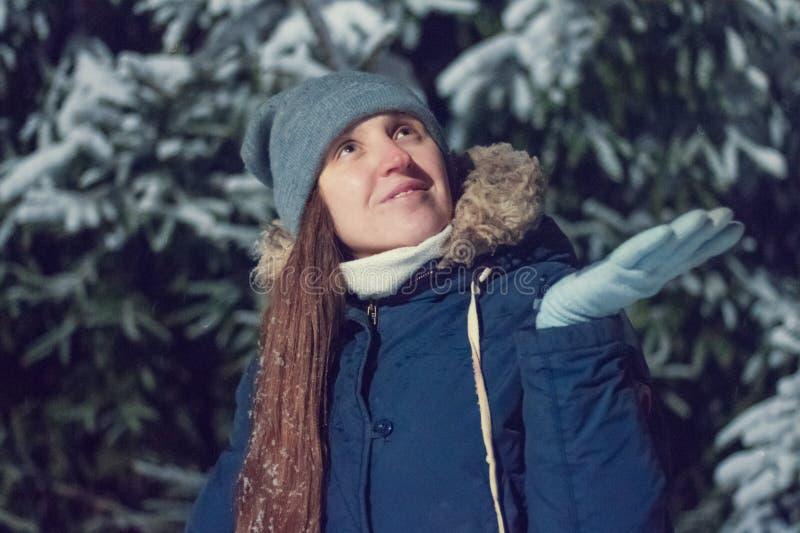 Vinterskönhetkvinnan fångar snöflingor i nattskog royaltyfri bild