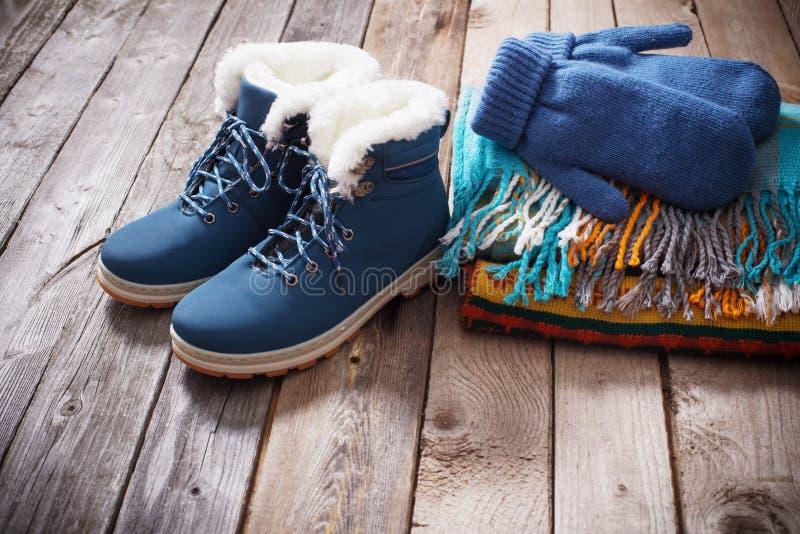 Vinterskor, handskar, scarves på gammal träbakgrund royaltyfri foto
