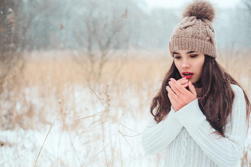 vinterslut upp ståenden av den härliga unga kvinnan i stuckit gå för hatt som och för tröja är utomhus- royaltyfri foto