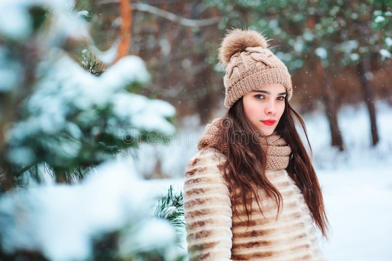 vinterslut upp ståenden av den härliga unga kvinnan i stuckit gå för hatt som och för tröja är utomhus- arkivfoto